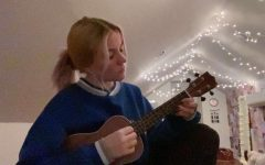 Junior Emma Meredith is practicing her ukulele. She likes to play it while singing.