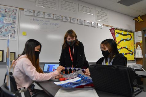 Science teacher Amanda Schnepp discusses the structure of a double helix DNA model with students in her Biology class.