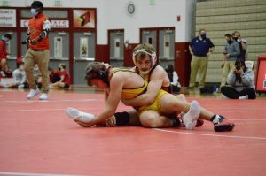 Senior Luke Goodwin wrestles his opponent during the first match of the Conference Indiana tournament. Goodwin placed second in the tournament, and his points helped lead the team to a fourth place finish.