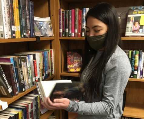 Junior Naomi Chan is helping out in the library. She enjoys reading instead of being on her phone.