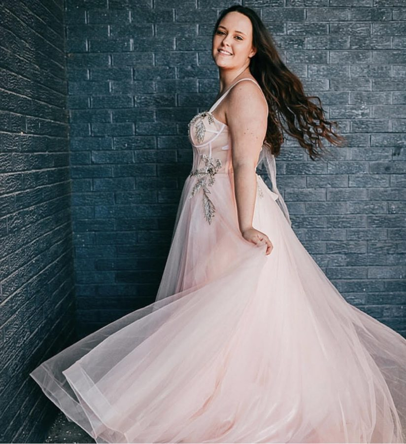 Sophomore Kaitlynn Miner poses in one of Sophia's floral prom dresses. Minor says that having photoshoots makes her feel more confident.