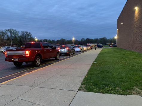 On the morning of April 13, cars wait in line to drop off students.