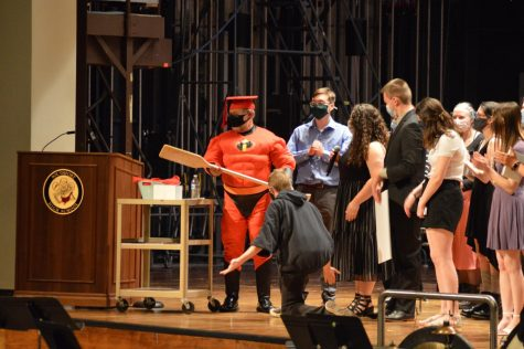 Band teacher David Copeland, in a superhero suit, receives gifts from his senior band students at their final concert. They bought him a paddle to represent his love for the outdoors.