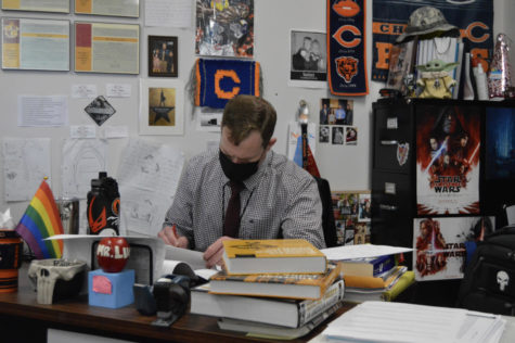 Social studies teacher David Luers grades papers at his desk. He is not a big fan of the new grading system.