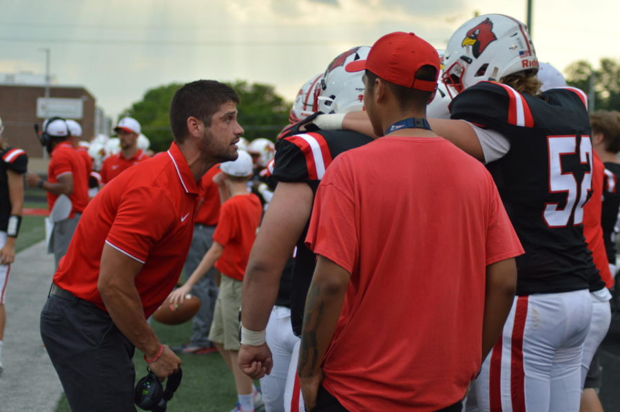 Assistant coach Micah Brown encourages his players to do their best before kickoff against PMHS on Aug. 27. The Cards  lost 42- 7.