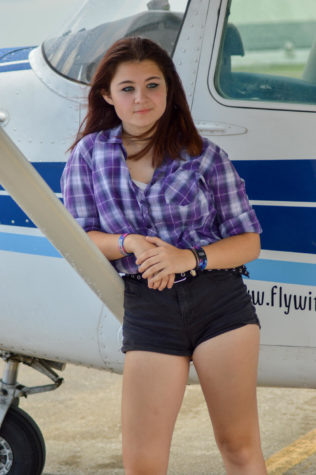 Sophomore Katie Essex poses in front of one the planes she flies. She hopes to fly without an instructor soon.